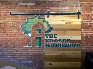 Custom signs in Livonia, installed farm-door style wooden sign on brick wall with custom painting